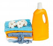 folded cotton clothes with raw cotton and detergent bottle