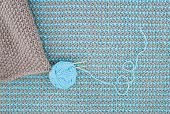 picture of knitwear  - Brown knitwear with knitting needles are on the background of turquoise knitwear - JPG