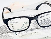 Financial Chart And Graph Of Stock Indexes See Through Glasses Lens On Financial Newspaper