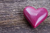 image of marsala  - one marsala pink heart laying on wooden background