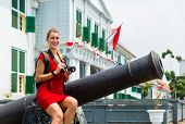 picture of cannon  - Woman tourist  sitting on cannon in old Batavia colonial district of Jakarta - JPG