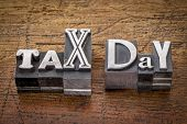 tax day - financial concept - words in mixed vintage metal type printing blocks over grunge wood