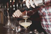 Bartender is straining drink in a glass, toned, misty, bleached colors