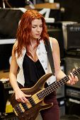 music, sale, people, musical instruments and entertainment concept - female musician or customer playing bass guitar at music store