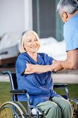 Happy senior woman being assisted by male nurse to get up from wheelchair at nursing home yard