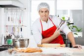 Portrait of confident male chef holding tongs while preparing ravioli pasta at counter in commercial kitchen