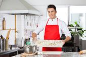 Portrait of smiling male chef holding uncooked ravioli pasta on cutting board in commercial kitchen