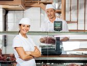 Portrait of confident female butcher with male colleague weighing meat at shop