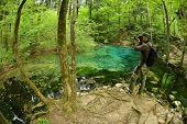 photographer visiting beautiful pond in the woods, Ociul Beiului, Caras Severin county, Romania