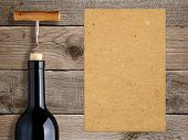 Bottle Of Wine With Corkscrew And Blank Paper On Wooden Background