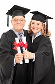 Mature couple in graduation gowns holding diplomas isolated on white background