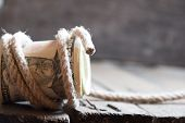 pic of fifties  - American Fifty Dollar Bills rolled up and rope on a wooden table - JPG