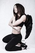 stock photo of camisole  - Young woman with a black wings over grey background - JPG