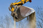 foto of excavator  - Close up of excavator bucket scooping gravel from pile for road construction - JPG