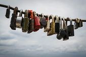 pic of cloudy  - Various locked steel padlocks on a secure tough iron rod against a cloudy sky  - JPG