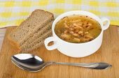 stock photo of tablespoon  - Pea soup with bread and tablespoon on wooden board - JPG