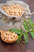 image of chickpea  - Chickpea varieties in a burlap bag with green sprouts on a wooden background - JPG