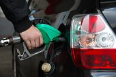 picture of fuel economy  - Male Hand Refilling the black Car with Fuel on a Filling Station - JPG