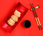 image of siomai  - Vietnam style steamed shrimp dumplings served on a red background - JPG