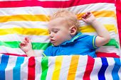picture of pretty-boy  - Child sleeping in colorful bed - JPG