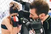 stock photo of sparring  - mma training. couple making sparring in the mma cage. concept about fighting fitness and sport