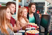 stock photo of popcorn  - It is cool. Four young persons buying popcorn and drinks before watching film in cinema.
