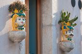 stock photo of planters  - Characteristic ceramic head shaped flowered planters set into the stone wall of a house along the streets of Castelmola Sicily  - JPG