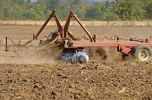 image of cultivation  - Farmer using a disc cultivator to break of soil after plowing on a field in Oregon - JPG