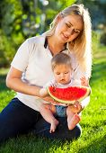 stock photo of mother baby nature  - Young happy mother and her baby daughter eating watermelon outdoors  - JPG