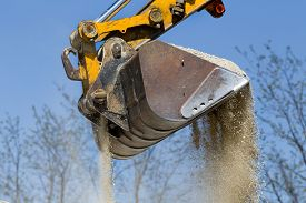 stock photo of excavator  - Close up of excavator bucket scooping gravel from pile for road construction - JPG