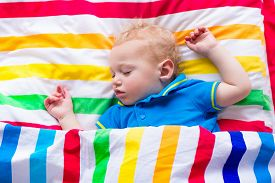 stock photo of sweet dreams  - Child sleeping in colorful bed - JPG