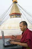 Side Profile Of A Monk Using A Laptop
