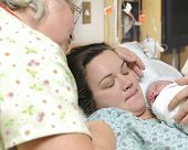Mother And Grandmother With Newborn Baby Right After Delivery