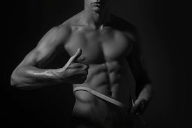image of nipples  - Young naked man with sexual strong muscular beautiful body with sexy chest and nipples with tape measure round waist holding thumb up standing in studio black and white horizontal picture - JPG