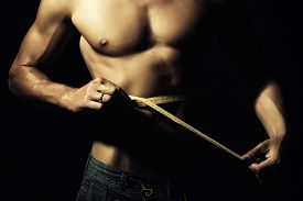 picture of nipples  - Closeup of young naked boy in jeans with sexual strong muscular beautiful tan body with sexy chest and nipples holding yellow tape measure round waist standing on black background horizontal picture - JPG