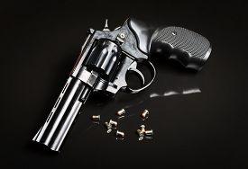 stock photo of revolver  - Revolver gun on black background with bullets - JPG
