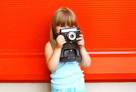 picture of little girls photo-models  - Little smiling girl child with old retro vintage camera against the colorful red wall - JPG
