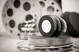 foto of mm  - Heap of old 35 mm movie reels with out of focus clapper and boxes in background vintage black and white - JPG