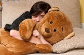 Young Woman Embracing Teddy Bear Lying On On Sofa Close-up