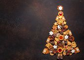 Assorted Christmas cookies in the shape of a Christmas tree on brown background. Top view. poster