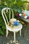 stock photo of shabby chic  - Shabby chic chair in garden with flowers and flowery hat - JPG