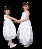 stock photo of fraternal twins  - adorable twin sisters in white gowns haolding hands - JPG