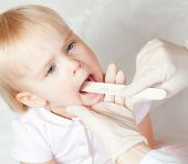 Pediatrician examining little girl's throat with tongue depressor