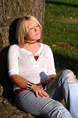Blond Woman Sitting And Sunning Herself By Tree