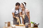 Affectionate Female Going To Kiss Hard Working Husband Who Makes Dough And Helps Her At Kitchen. Lov poster
