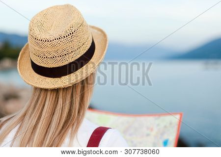 poster of Traveler Is Looking At Map At Sea Beach. Woman Tourist Is Traveling. Girl In Straw Hat Is Enjoying S