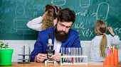 Man Bearded Teacher Work With Microscope And Test Tubes In Biology Classroom. Explaining Biology To  poster