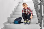 Front View Of Sad Blond Boy Sitting On Stairs In Corridor Of School And Leaning Head By Hand. Little poster