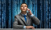 Young Man Talking On Phone And Looking Upward. Businessman Sitting At Desk On Background Abstract Bi poster