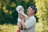 Young Grandfather Playing With Adorable Baby Girl Over A Nature Background. Grandparents And Grandch poster